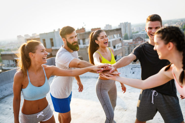 Group of fit happy people training outdoor on the roof